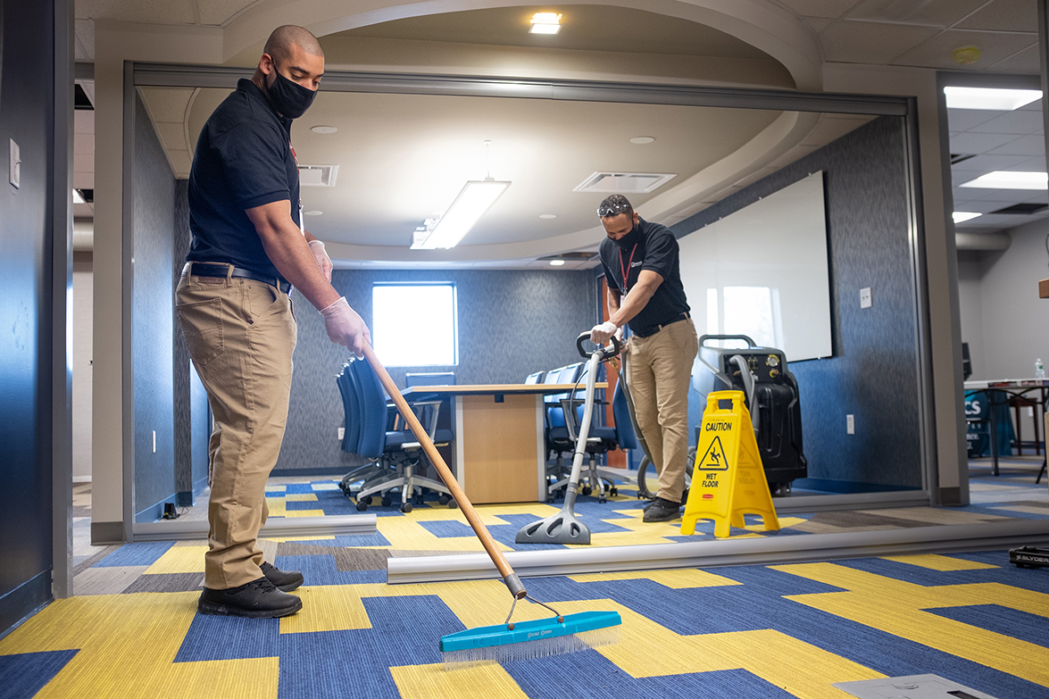 Professional carpet cleaning in an office wearing masks