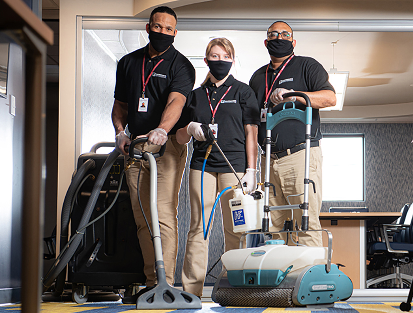 Professional carpet cleaning company wearing masks and disinfecting an office