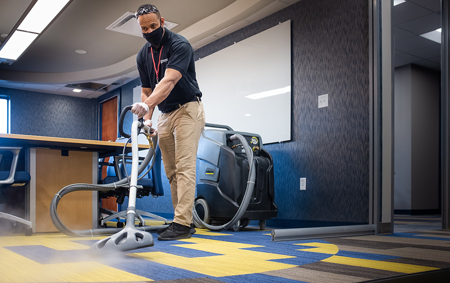 Man Steam Cleaning Office Carpet