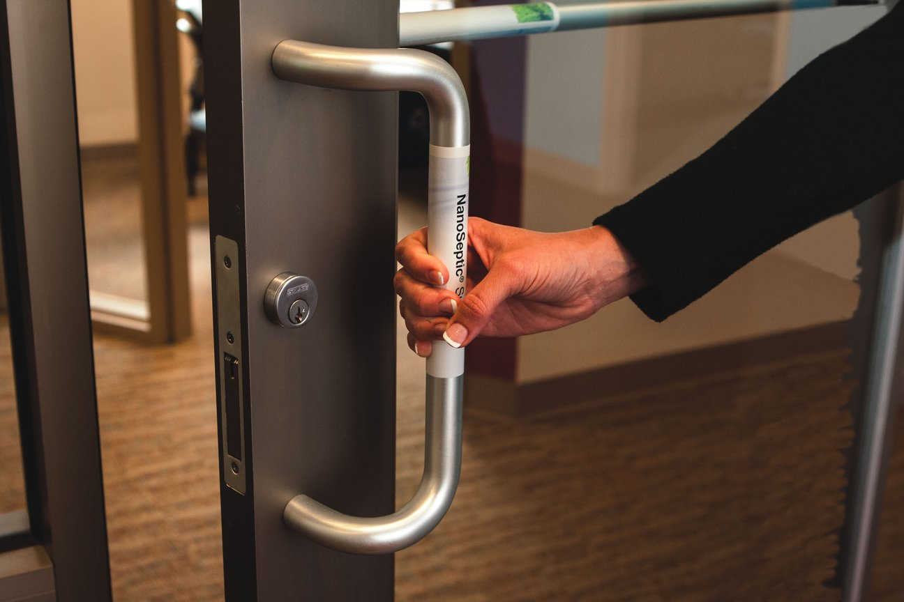 Woman opening office door with nanoseptic strip on handle