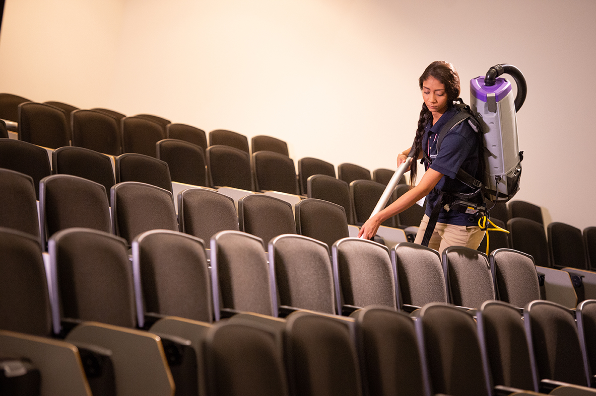 Woman cleaning lecture hall with backpack vacuum