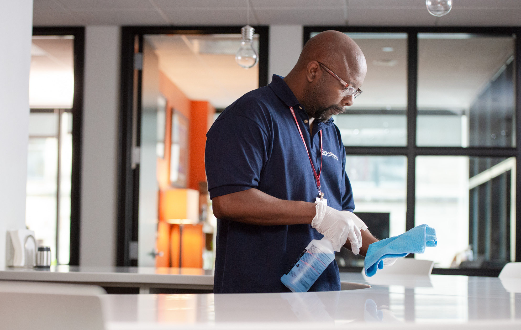 Janitronics employee spraying blue towel over counter